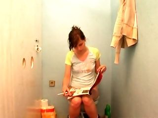 Amy sitting on a toilet when she sees a rod coming out of a glory-hole